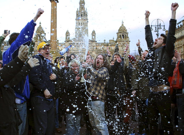 "Revellers spray a bottle of champagne as they celebrate the death of former British prime minister Margaret Thatcher, at George Square in Glasgow, Scotland April 8, 2013. Margaret Thatcher, the ""Iron Lady"" who transformed Britain and inspired conservatives around the world by radically rolling back the state during her 11 years in power, died on Monday following a stroke. She was 87. (Photo by David Moir/Reuters)"
