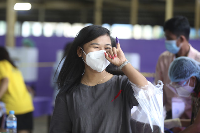 A voter wearing protective face mask shows off her finger marked with ink indicating she voted as she leaves a polling station Sunday, November 8, 2020, in Yangon, Myanmar. Voting was underway in Myanmar's elections on Sunday, with the party of Nobel Peace Prize laureate Aung San Suu Kyi heavily favored to retain power it had wrestled from the powerful military five years ago. (Photo by Thein Zaw/AP Photo)