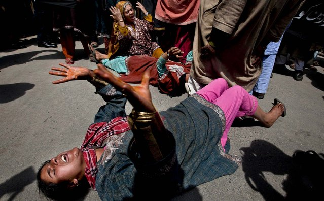 Kashmiri Muslim women relatives of prisoner Mohammad Ismail Shah shout slogans against the police as they block a road during a protest in Srinagar, India, Friday, April 12, 2013. More than a dozen relatives and neighbors of Shah protested against the police alleging he was beaten and killed by police in prison. Police refuted the charges saying Shah was killed by another prisoner. (Photo by Dar Yasin/AP Photo)