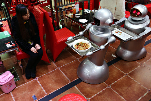 Two 70 thousand RMB (about 11,310 USD) robots carry dishes and offer service for customers at a robot themed restaurant at Chunxi Road in Chengdu, China, December 11, 2014. The restaurant has 10 robots to serve as waiters. Each robot can carry simple dishes and offer simple greetings. (Photo by ChinaFotoPress/ChinaFotoPress via Getty Images)