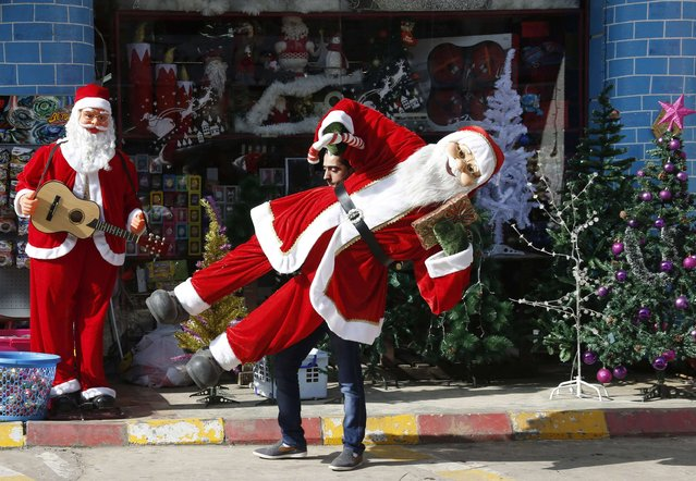 A shop vendor carries a Santa Claus toy in front of his shop in Nabatiyeh, in south Lebanon December 14, 2014. (Photo by Ali Hashisho/Reuters)