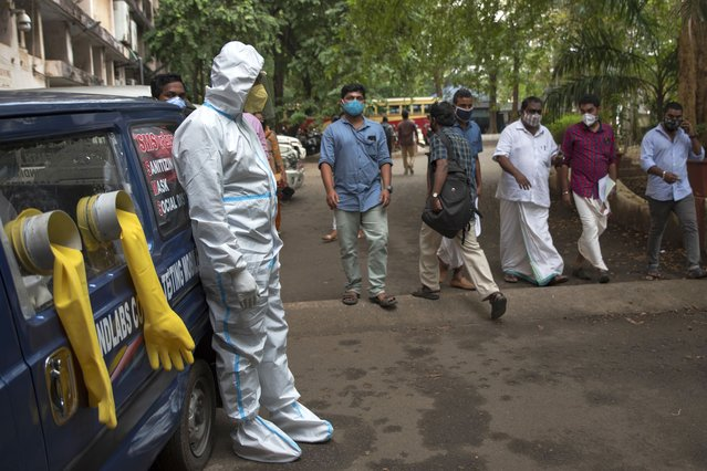 A man in protective suit stands next to a mobile COVID-19 testing kiosk outside the Ernakulam district administration headquarters in Kochi, Kerala state, India, Wednesday, November 18, 2020. A country of nearly 1.4 billion people, India is the world's second most coronavirus affected country after the United States. (Photo by R.S. Iyer/AP Photo)