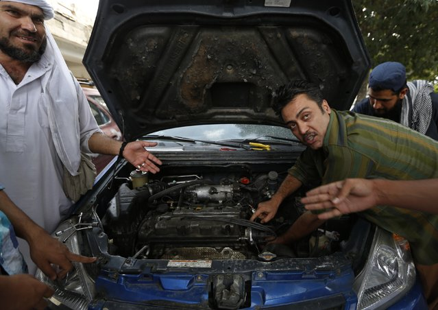 An instructor explains a car's mechanics during a technical lesson at a driving school in Kabul August 24, 2014. (Photo by Mohammad Ismail/Reuters)