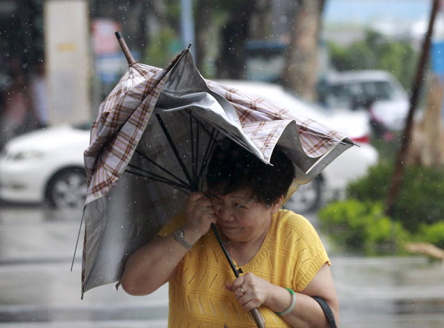 A woman holds her umbrella while walking against strong winds as Typhoon Soudelor hits Taipei, Taiwan, August 8, 2015. (Photo by Pichi Chuang/Reuters)