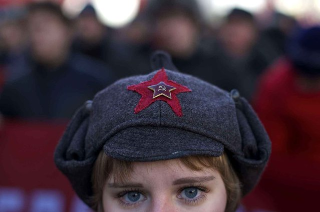 A girl wears a hat with a Soviet-era insignia as she takes part in a Communist demonstration marking the 98th anniversary of the Bolshevik revolution in Moscow, Russia, Saturday, November 7, 2015. For decades Nov. 7 used to be a holiday celebrating the 1917 Bolshevik Revolution and which is no longer a public holiday in Russia. (Photo by Ivan Sekretarev/AP Photo)