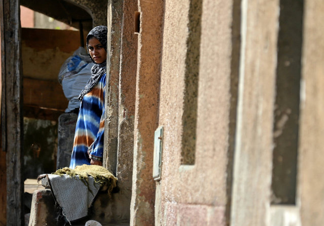 A woman stands in front of her home in Ezbet Khairallah in Cairo, Egypt October 4, 2016. (Photo by Mohamed Abd El Ghany/Reuters)