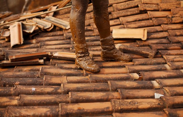 A firefighter stands on the roof of a destroyed  house, in Bento Rodrigues district after a dam, owned by Vale SA and BHP Billiton Ltd burst, in Mariana, Brazil, November 9, 2015. Mud and waste water from burst dams at a Brazilian iron ore mine cut off drinking water and raised health and environmental concerns in cities more than 300 km (186 miles) downstream on Monday, amid increasingly dire search efforts in a village devastated by the mudslides. (Photo by Ricardo Moraes/Reuters)