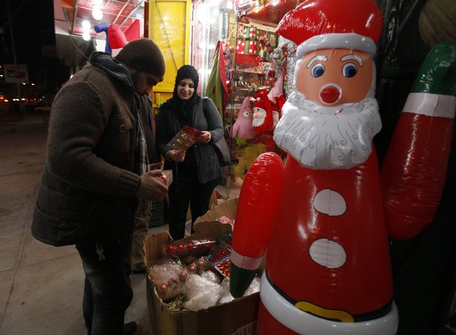 Iraqi people shop for Christmas decorations at a market in Baghdad, December 24, 2014. (Photo by Ahmed Saad/Reuters)