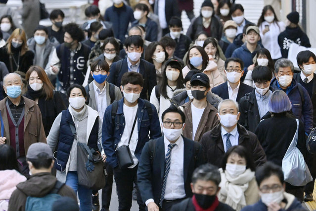 People wear face masks as they make their way through a street in Tokyo Friday, November 27, 2020. Tokyo reported 570 new COVID-19 cases on Friday, a new record for Japan's capital city as the country faces a surge in infections. (Photo by Yohei Nishimura/Kyodo News via AP Photo)