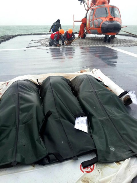 A Basarnas helicopter is seen behind three covered bodies recovered from the AirAsia plane, on the deck of KRI Bung Tomo warship off the Java Sea, Indonesia, December 31, 2014 in this photo taken by Antara Foto. A body recovered on Wednesday from the crashed AirAsia plane was wearing a life jacket, an official with Indonesia's search and rescue agency said, raising questions about how the disaster unfolded. (Photo by Lettu Solihin/Reuters/Antara Foto)