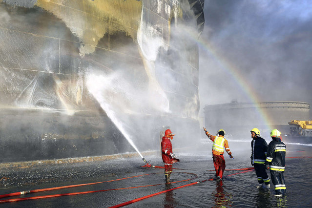 A rainbow is seen as fire-fighters work to put out a fire at a storage oil tank in the port of Es Sider January 2, 2015. Libya has extinguished a fire at oil storage tanks at the country's biggest oil port, Es Sider, that had been raging for a week, officials said on Friday. (Photo by Reuters/Stringer)