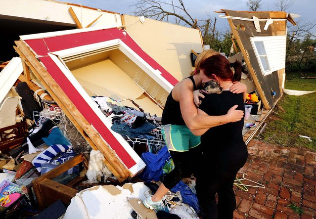 Alli Christian, left, returns Jessica Wilkinson's dog Bella to her after finding the pet amid the wreckage of Wilkinson's home shortly after a tornado struck in Norman on Sunday. (Photo by Steve Sisney/The Oklahoman)