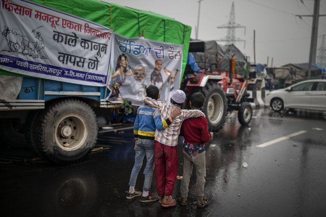 Young Indian boys look at posters critical of Indian government at a site of protest against new farm laws at the Delhi-Uttar Pradesh state border, India, Monday, January 4, 2021. (Photo by Altaf Qadri/AP Photo)