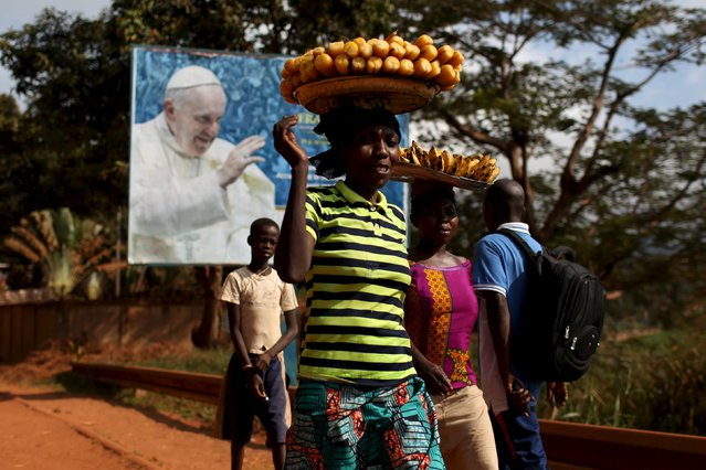 Women carrying fruits and vegetables on their heads walk past a billboard with a photograph of Pope Francis, in Bangui, Central African Republic, November 26, 2015. (Photo by Siegfried Modola/Reuters)