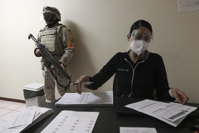 A soldier stands guard as healthcare workers are registered to receive shots of the Pfizer COVID-19 vaccine, on the first day of coronavirus vaccinations in Ciudad Juarez, Mexico, Wednesday, January 13, 2021. (Photo by Christian Chavez/AP Photo)