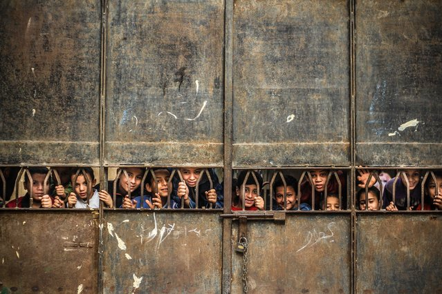 """""""Sneaky"""". Egyptian children living in one of Cairo's slums pose for a photo behind a school gate. (Photo and caption by Mosa'ab Elshamy/National Geographic Traveler Photo Contest)"""