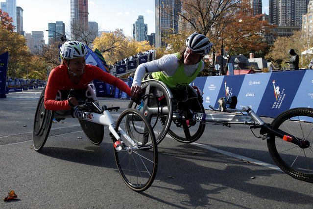 Winner Tatyana McFadden of the U.S. (R) holds hands with second place finisher Manuela Schar of Switzerland after the finish of the women's wheelchair division of the 2016 New York City Marathon in Central Park in the Manhattan borough of New York City, U.S., November 6, 2016. (Photo by Mike Segar/Reuters)