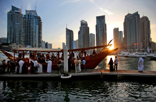 In this March 25, 2015 photo, tourists of different nationalities board a dhow for a cruise as the sun sets in the Marina neighborhood of Dubai, United Arab Emirates. Dubai's year-round sunshine gives the Marina a summer-vibe throughout the winter months, when temperatures rarely drop below a comfortable 75 degrees Fahrenheit (24 Celsius) during the day. (Photo by Kamran Jebreili/AP Photo)