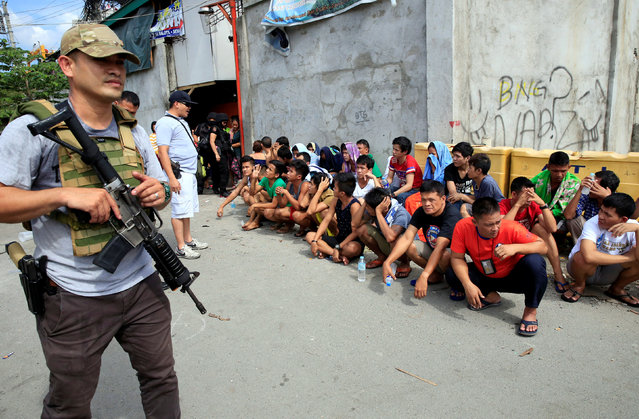 A police officer talks to male residents following an identity check during an anti-drugs operation in metro Manila, Philippines November 10, 2016. The men were later released. (Photo by Romeo Ranoco/Reuters)