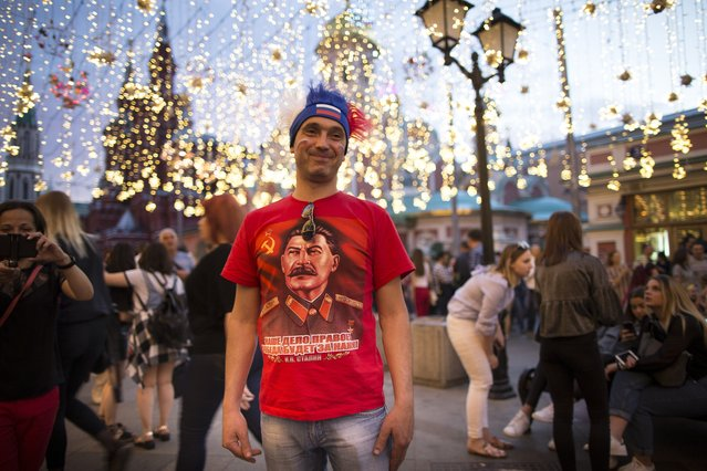 A Russia soccer fan in a red T-shirt with a portrait of former Soviet leader Josef Stalin poses for tourists in Reg Square in Samara, Russia, Monday, June 25, 2018, after the group A match between Uruguay and Russia at the 2018 soccer World Cup. (Photo by Alexander Zemlianichenko/AP Photo)