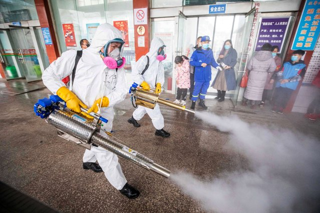 This photo taken on February 7, 2021 shows workers disinfecting a long distance bus station in Bijie, in China's southwest Guizhou province, as authorities prepare for a travel peak ahead of the Lunar New Year, which ushers in the Year of the Ox on February 12. (Photo by AFP Photo/China Stringer Network)
