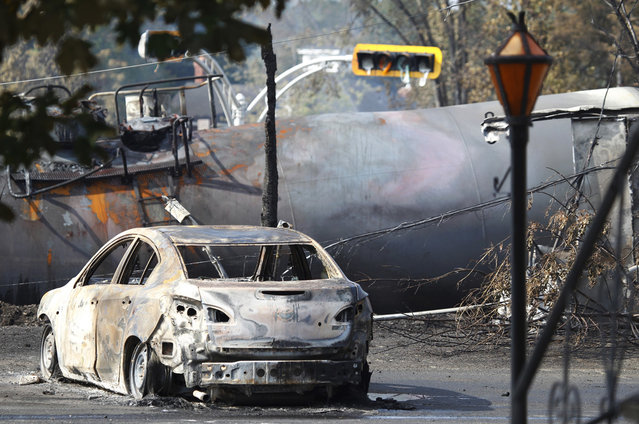 A burned vehicle sits near the wreckage of a train car and a melted traffic light, after a train derailment and fire in Lac-Megantic, on July 7, 2013. (Photo by Christinne Muschi/Reuters)