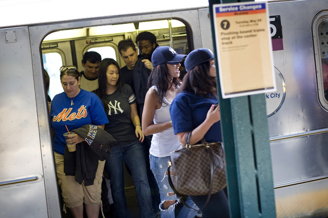 New York Mets and New York Yankees fans leave the No. 7 train as they attend the Subway Series interleague baseball game between the Mets and the Yankees at Citi Field in New York, May 21, 2010. (Photo by David Goldman/AP Photo)