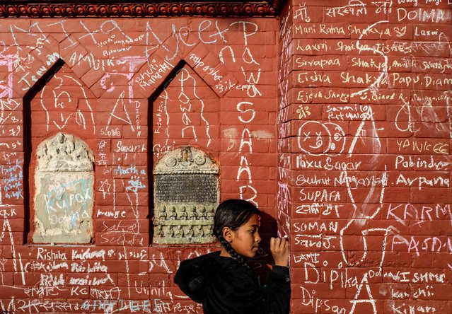 A girl writes on the wall of a Saraswati temple during the Shreepanchami festival dedicated to goddess of education Saraswati in belief that the goddess will help devotees excel in education, in Kathmandu, Nepal on February 16, 2021. (Photo by Navesh Chitrakar/Reuters)
