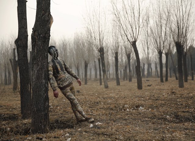 """A model painted in camouflage colours to blend in with the background practises posing for Chinese artist Liu Bolin's artwork """"Dongji"""", or Winter Solstice, on the second day after China's capital Beijing issued its second ever """"red alert"""" for air pollution, in Beijing, China, December 20, 2015. (Photo by Kim Kyung-Hoon/Reuters)"""