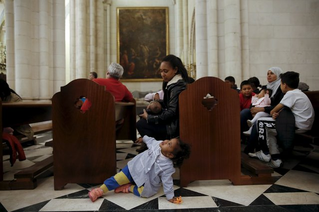 A girl plays before the start of a distribution of free toys for low-income families and a picture on the lap of one of the Three Wise Men at Almudena Cathedral in Madrid, Spain, December 22, 2015. (Photo by Susana Vera/Reuters)