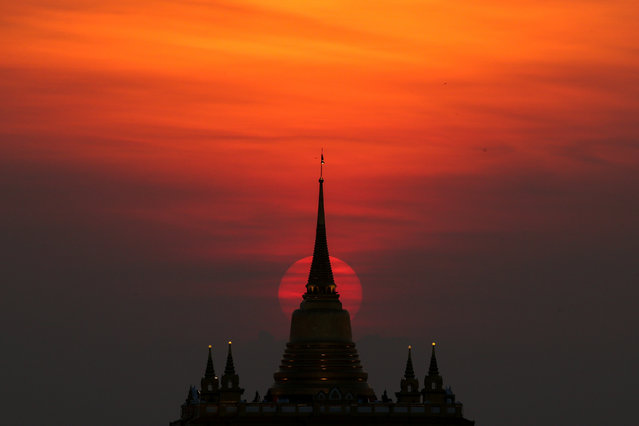 The sun sets behind Wat Saket Temple, or Golden Mount in Bangkok, Thailand on March 20, 2018. (Photo by Athit Perawongmetha/Reuters)