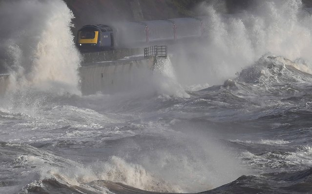 Waves hit a train during heavy seas and high winds in Dawlish in south west Britain, February 2, 2017. (Photo by Toby Melville/Reuters)