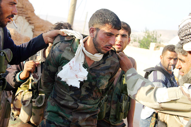 """A Syrian soldier is captured by """"Free Syrian Army"""" fighters during what the FSA say is an offensive against forces loyal to Syria's President Bashar al-Assad, in Qobtan village in Aleppo August 22, 2013. (Photo by Saad AboBrahim/Reuters)"""
