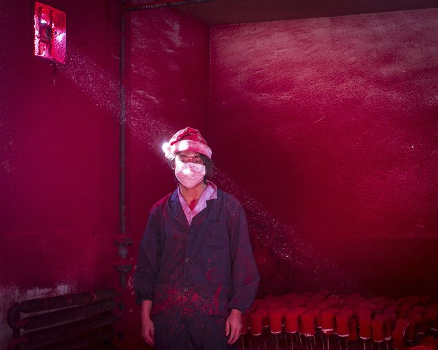 Ronghui Chen, Chinese photographer of City Express, won the Second Prize in the Contemporary Issues Category, Singles, of the 2015 World Press Photo contest with this picture of Wei, a 19-year-old Chinese worker, wearing a face mask and a Santa hat, standing next to Christmas decorations being dried in a factory as red powder used for colouring hovers in the air, in Yiwu, China, in this picture taken December 6, 2014, and released by the World Press Photo on February 12, 2015. (Photo by Ronghui Chen/Reuters/City Express/World Press Photo)
