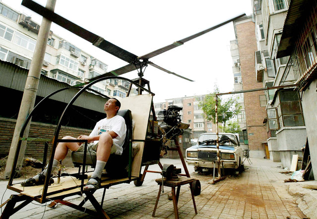 """A self-styled Chinese inventor tests his homemade helicoptor next to his apartment in Beijing June 25, 2003. Yu Jun follows in the footsteps of his younger brother who lost his life in a national park in central China at the end of a 20 year search for the legendary """"Bigfoot"""", and intends to continue the quest from the sky. Without any formal education in aerospace science, Yu Jun spent five years constructing the helicopter from spare parts belonging to a dilapidated """"Lada"""" automobile (in back). (Photo by Reuters/China Photo)"""