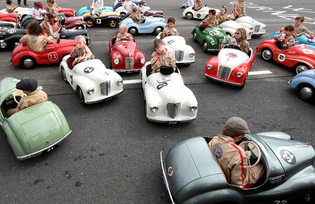 Children react after competing in a pedal car race as motoring enthusiasts attend the Goodwood Revival, a three day classic car racing festival celebrating the mid-20th century heyday of the sport, at Goodwood in southern Britain on September 9, 2018. (Photo by Toby Melville/Reuters)