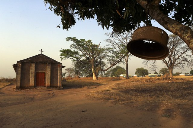 A church bell hangs from a tree brunch outside a catholic church and a school in Odek village, north of Uganda capital Kampala February 14, 2015. (Photo by James Akena/Reuters)