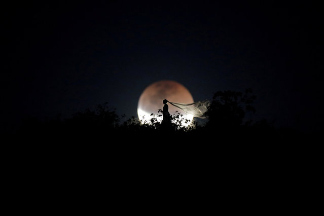 A bride poses for photo during a total lunar eclipse from in Brasilia, Brazil, July 27, 2018. (Photo by Ueslei Marcelino/Reuters)