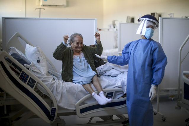 """Blanca Ortiz, 84, celebrates after learning that she will be dismissed from the Eurnekian Ezeiza Hospital, on the outskirts of Buenos Aires, Argentina, Thursday, August 13, 2020, several weeks after being admitted with COVID-19. Photographer Natacha Pisarenko said the moment was one of the few she witnessed in months of covering COVID-19 in which doctors and nurses allowed themselves to feel joy. """"The moment made all of us in the room with her laugh and feel hopeful again"""", Pisarenko said. """"It was the brightest moment for me while covering such a heavy story"""". (Photo by Natacha Pisarenko/AP Photo)"""
