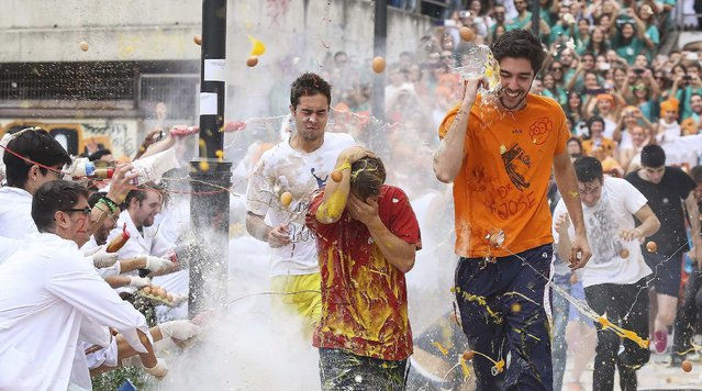 Faculty of medicine first year students run while seniors spray them with different types of sauces, liquids, flour and eggs as part of an annual tradition during a celebration in honour of their patron Saint Lucas at Granada University in Granada, southern Spain October 17, 2013. (Photo by Pepe Marin/Reuters)