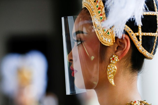 A performer wearing a face shield looks on during a ceremony held by the Bangkok National Museum to celebrate the return of two ancient relics, believed to have been stolen from Thailand about 60 years ago, from the United States, in Bangkok, Thailand on May 31, 2021. (Photo by Soe Zeya Tun/Reuters)