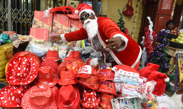 A female roadside vendor dressed in the traditions of Christmas gift- bringers displays her Christmas wares in Lagos, on December 24, 2016. .Nigerians are making last minute shopping to celebrate Christmas despite the economic recssion which has resulted in the high cost of gift items, decoratives and food stuff across the country. (Photo by Pius Utomi Ekpei/AFP Photo)