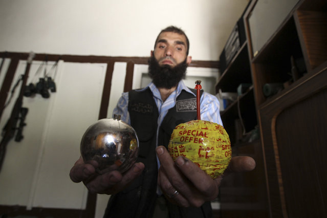 A Free Syrian Army fighter displays homemade bombs made from ornamental balls in the old city of Aleppo July 6, 2013. (Photo by Muzaffar Salman/Reuters)