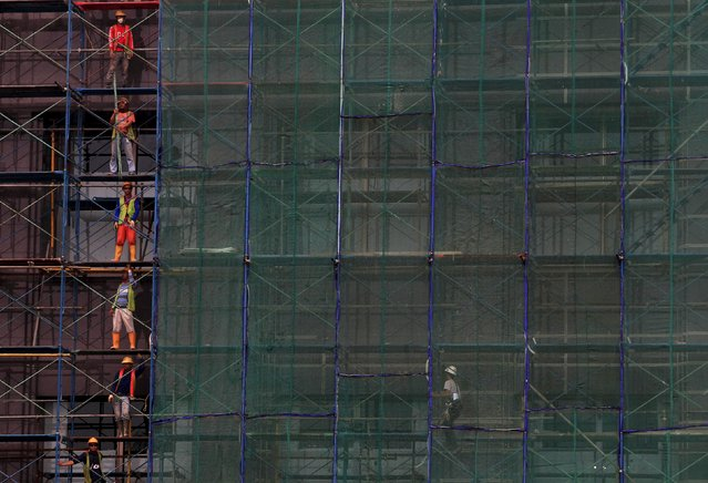 Workers stand in a scaffolding of a new building being constructed in Jakarta in this March 23, 2014 file photo. Indonesia is expected to report GDP numbers this week. (Photo by Reuters/Beawiharta)