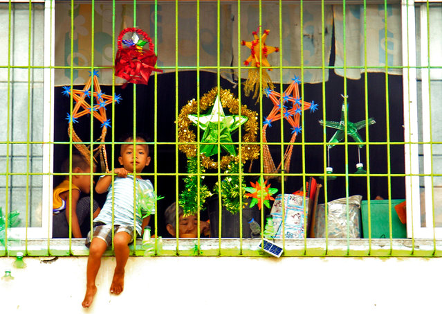 A boy sits at a window as he celebrates Christmas Day at the evacuation center before Typhoon Nock-ten is expected to strike Legazpi City, Albay province, central Philippines December 25, 2016. (Photo by Reuters/Stringer)