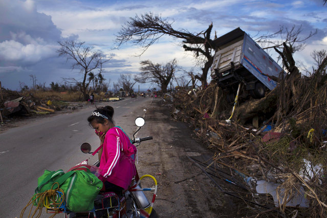 A woman rests on a roadside with her family's belongings near the Typhoon Haiyan ravaged town of Tacloban, central Philippines on Wednesday, November 13, 2013. Typhoon Haiyan, one of the most powerful storms on record, hit the country's eastern seaboard on Friday, destroying tens of thousands of buildings and displacing hundreds of thousands of people. (Photo by David Guttenfelder/AP Photo)