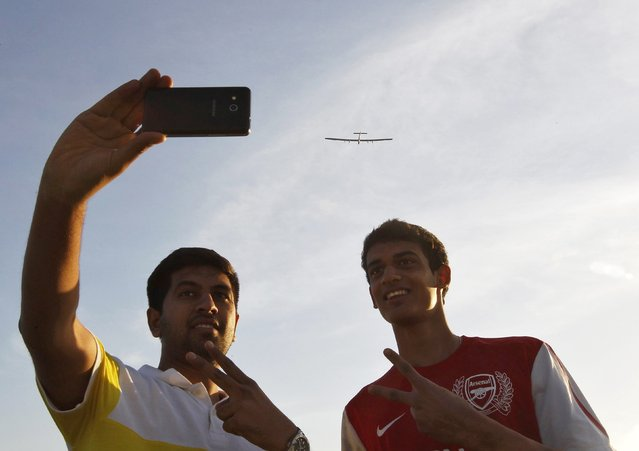 Two youths take a picture of themselves as the Solar Impulse 2, a solar powered plane, ascends in the sky behind them after taking off at the airport in the western Indian city of Ahmedabad March 18, 2015. (Photo by Amit Dave/Reuters)