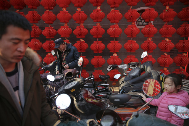 People pick up their motorcycles in front of decoration at the Longtan park as the Chinese Lunar New Year, which welcomes the Year of the Monkey, is celebrated in Beijing, China February 9, 2016. (Photo by Damir Sagolj/Reuters)