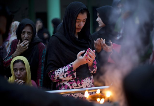 Pakistani women pray at the shrine of famous saint Shah Chun Chirag in Rawalpindi, Pakistan, Thursday, April 2, 2015. People usually visit shrines on Thursday and Friday to get their wishes fulfilled. (Photo by B. K. Bangash/AP Photo)