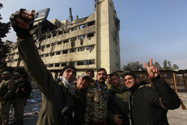 Iraqi rapid response forces take a selfie picture outside a hospital damaged by clashes during a battle between Iraqi forces and Islamic State militants in the Wahda district of eastern Mosul, Iraq, January 8, 2017. (Photo by Alaa Al-Marjani/Reuters)